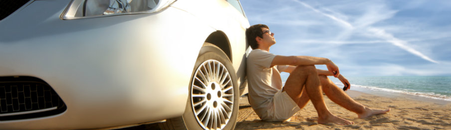 man sitting beside his car rental on the beach