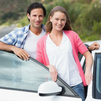 happy couples standing outside of their rental car