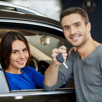 a man holding the key and woman sitting in the car