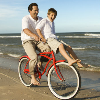 dad riding bike with his son on the beach