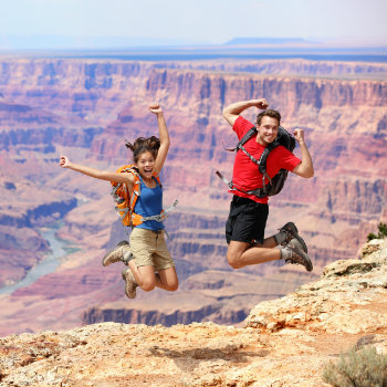 Happy couple jumping in Grand Canyon