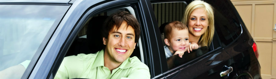 happy family riding in a black car