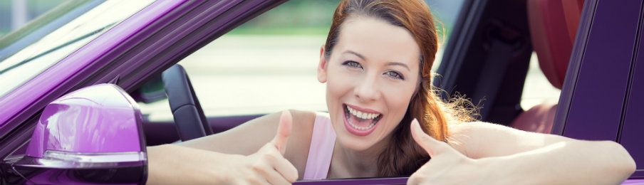 smiling woman posing inside her new purple car