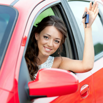 happy woman inside her red car holding key