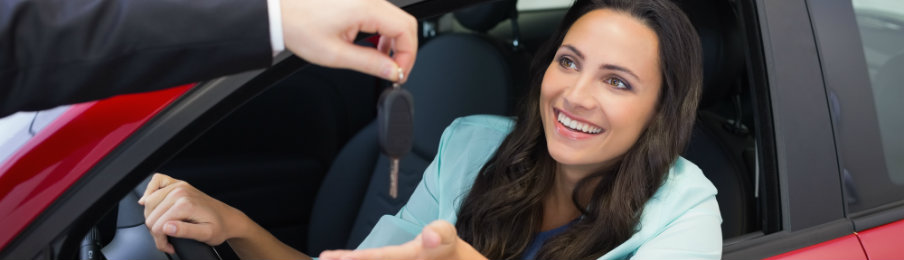 happy woman receiving the key to her rental car