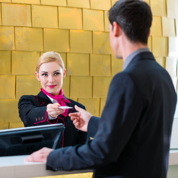 man getting card from hotel receptionist