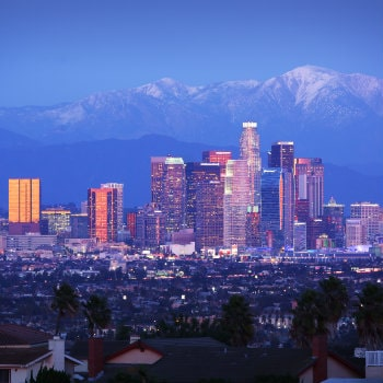 los angeles skyline over snowy mountains
