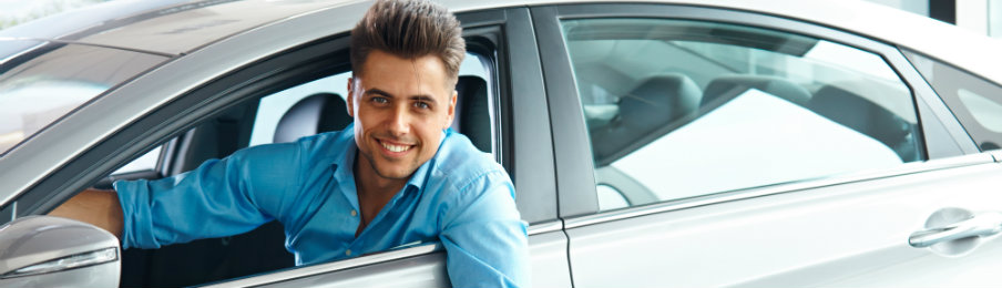 young male professional driving a rental car
