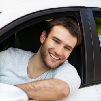 man inside white car smiling