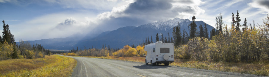 white motorhome on the road with scenic backdrop