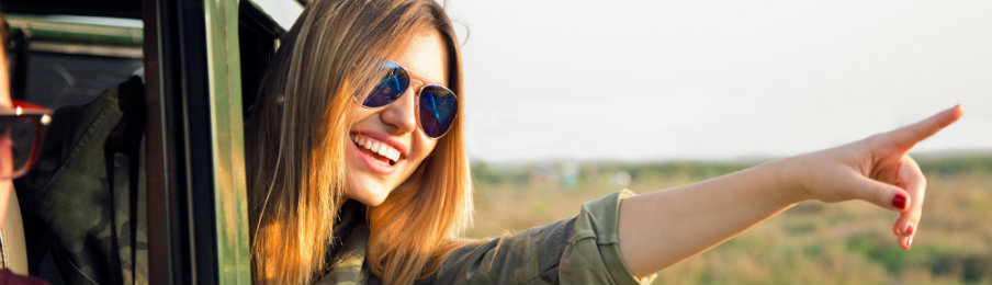 happy traveler pointing to something outside her rental vehicle