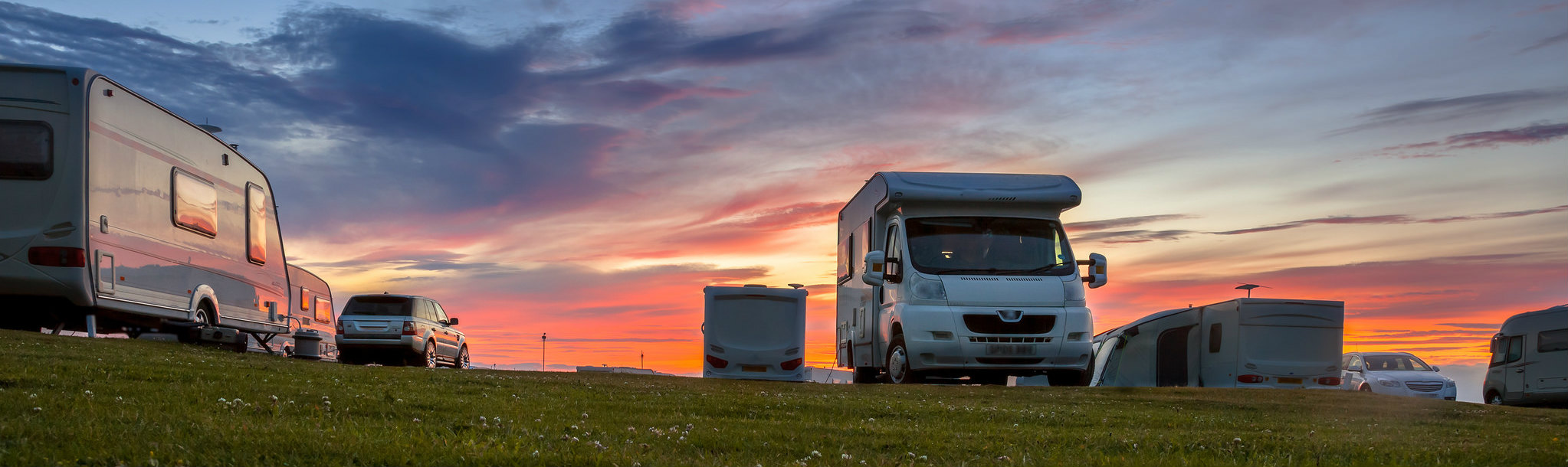 RV and motorhome rentals parked on a grassy area at dawn