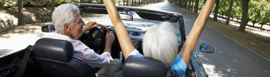 travelling senior couple in a sports car