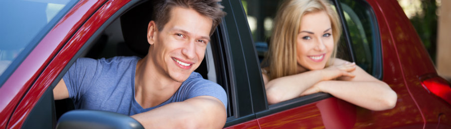 smiling couple inside a red car rental