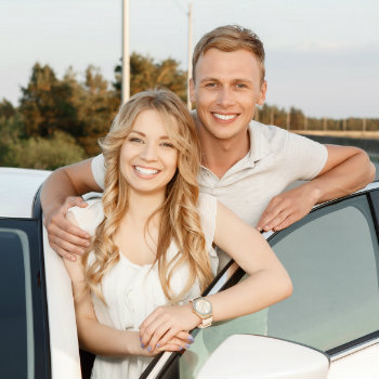 smiling couple with their white car