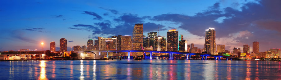 view of the urban skyscrapers and bridge over sea in miami taken at dusk